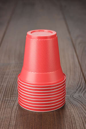 table of contents: stack of disposable red plastic cups on the wooden table