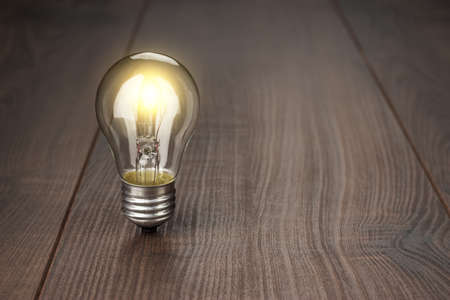 glowing bulb standing on the brown wooden background