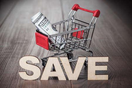 carretilla de mano: cien d�lares en el concepto de ahorro de carrito de la compra Foto de archivo