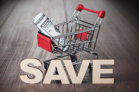 pushcart: one hundred dollars in the shopping trolley saving concept Stock Photo
