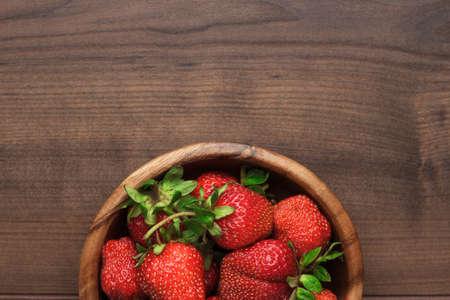 fresa: cuenco de madera lleno de fresas frescas en la mesa de color marrón Foto de archivo