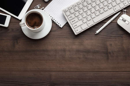 office table with notebook, computer keyboard, mouse, cup of coffee, tablet pc and smartphone. copy space