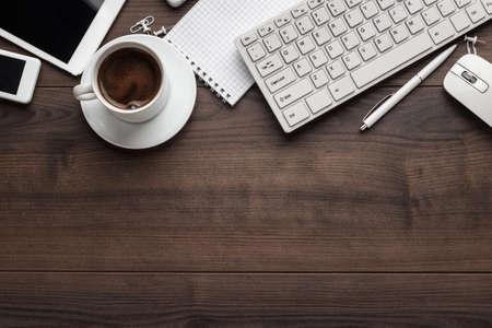 ordinateur bureau: table de bureau avec ordinateur portable, clavier d'ordinateur, souris, tasse de café, Tablet PC et smartphone. copie espace