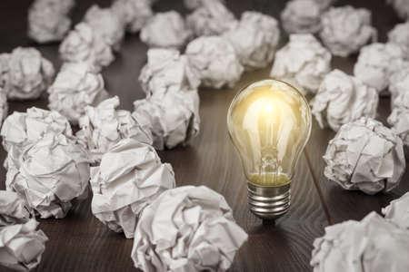 概念: 偉大的概念,皺巴巴的辦公用紙和燈泡站在桌子