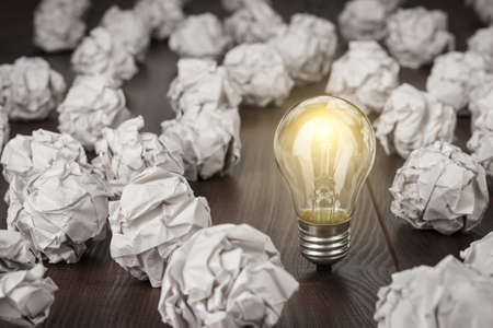 great concept with crumpled office paper and light bulb standing on the table. Stock Photo