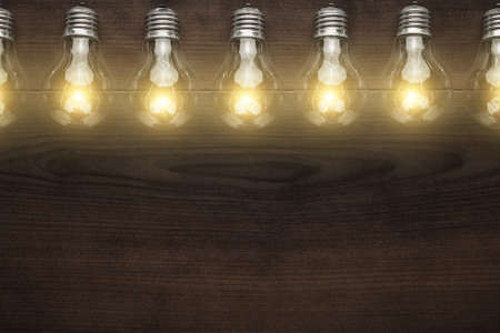 glowing bulbs over wooden background with copy space Stock Photo