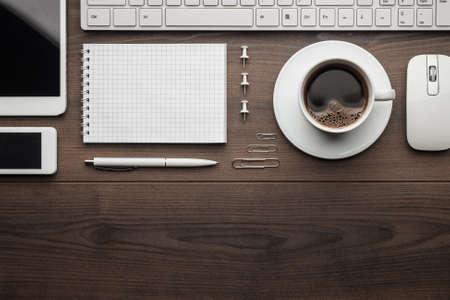 overhead van essentiële Office-objecten met het oog op houten bureau met een kopie ruimte