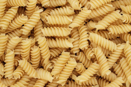 short pasta: close-up of dry uncooked rotini corkscrew-shaped pasta on the table texture background