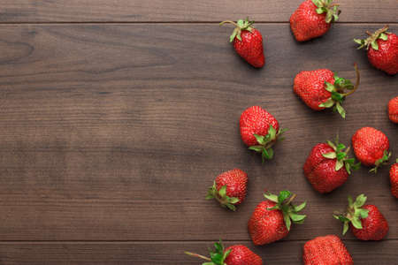 overhead view: fresh strawberries on the brown wooden table Stock Photo