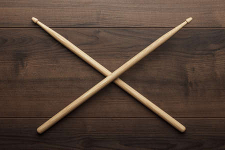 bateria musical: par de baquetas de madera cruzados sobre la mesa de madera