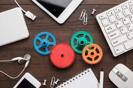 sistemas: flujo de trabajo y el trabajo en equipo los conceptos con los engranajes de colores diferentes aparatos y material de oficina en la mesa de madera