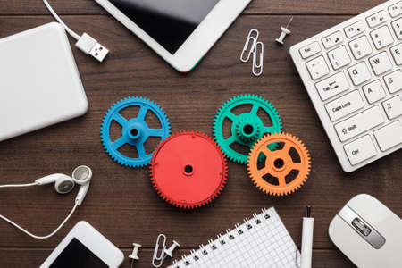 business gears: workflow and teamwork concepts with colorful gears different gadgets and office stationery on the wooden table