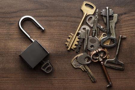 llaves: check-cerradura se abrió y diferentes teclas en madera del concepto del fondo Foto de archivo