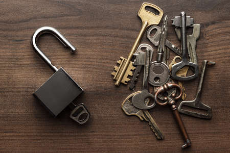 old keys: opened check-lock and different keys on wooden background concept