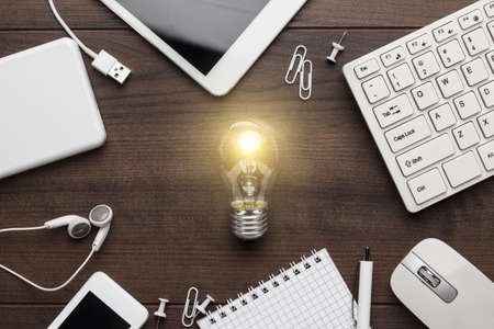 lightbulbs: creative process concept with different gadgets and office stationery on the wooden table