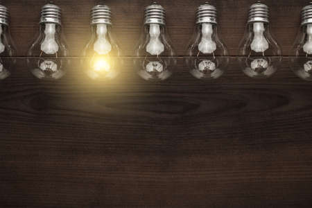 lightbulbs: glowing bulb uniqueness concept with copy space on brown wooden table
