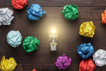 best idea concept with crumpled colorful paper and light bulb on wooden table Foto de archivo