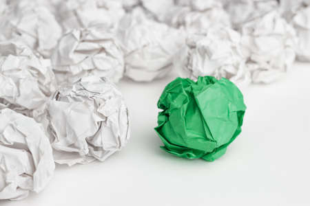 bright ideas: overhead shot of crumpled paper in oder and green one standing out. great idea concept on the white office table Stock Photo
