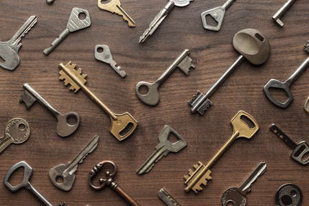 overhead of many different keys in oder on wooden background concept Фото со стока