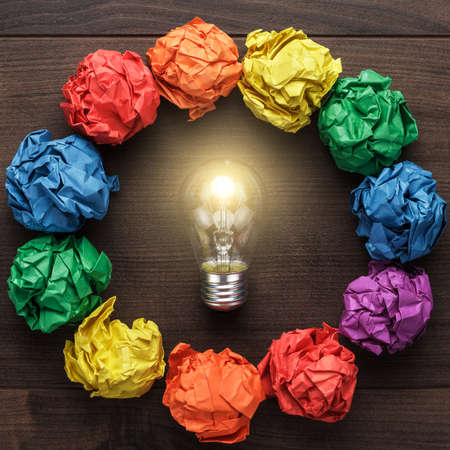 solution: best idea concept with crumpled colorful paper circle and light bulb in the centre on wooden table