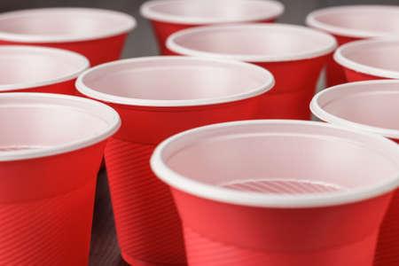 木製のテーブルに使い捨ての赤いプラスチック カップ