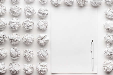 crumpled paper: blank sheet of paper on the white table with a pen creative process concept