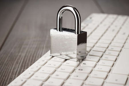 password protection: padlock and white computer keyboard on the wooden office table. privacy protection, encrypted connection concept