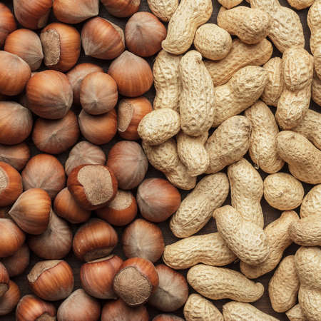 unbroken: peanuts and hazelnuts on the table background Stock Photo