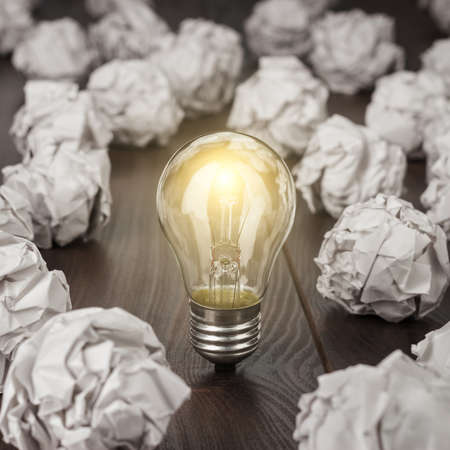 great: great concept with crumpled office paper and light bulb standing on the table Stock Photo