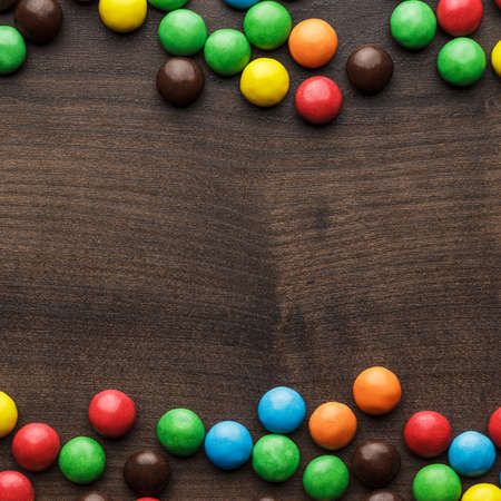 overturn: colorful sweets on the brown wooden table background