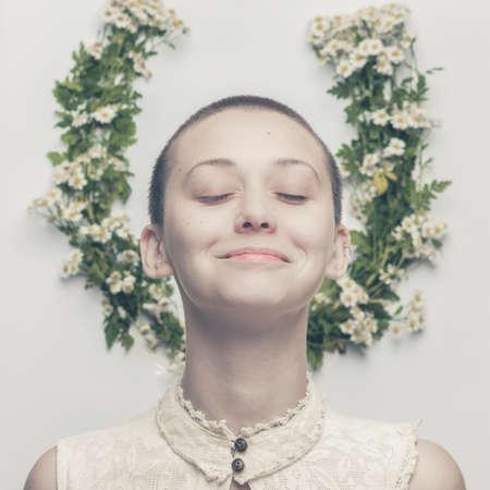 bald: retrato de la hermosa muchacha sonriente calva de cabeza sobre el fondo floral