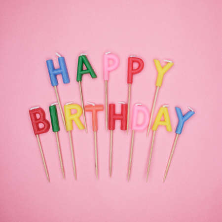 happy birthday candles: colorful letter-shaped happy birthday candles on pink background