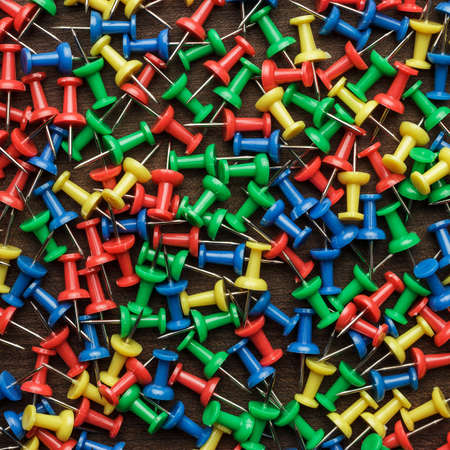 push in pins: bright colorful push pins on wooden background texture Stock Photo