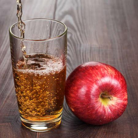 vaso de jugo: jugo de manzana fresca vierte en el vidrio en la cocina Foto de archivo