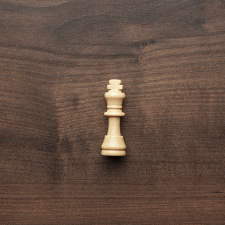 chess player: white chess king on the wooden table background