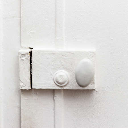 white door: closed door with old vintage white painted lock close-up Stock Photo