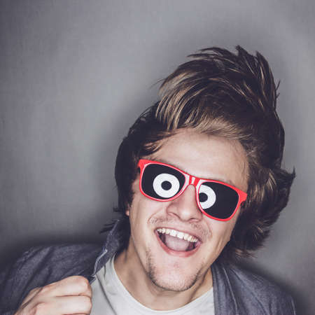 cool man: casual young man with sunglasses shaking his head