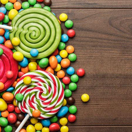 paleta de caramelo: diferentes colores y dulces piruletas en la mesa de madera Foto de archivo