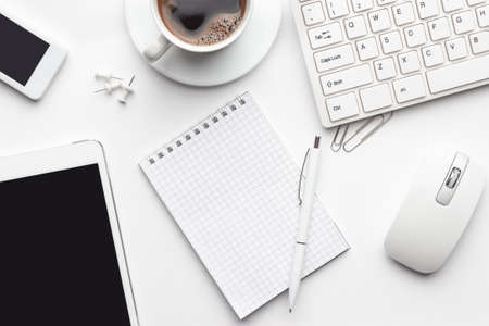 sobrecarga da mesa de escritório branco com notebook, teclado e mouse de computador, tablet pc e smartphone Foto de archivo