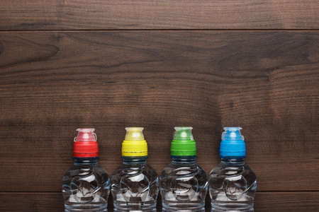 water bottles: plastic water bottles with caps of different colour on the wooden table