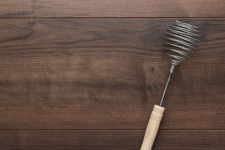 egg whisk: retro egg whisk with wooden handle on brown table with copy space