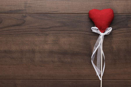 wooden stick: red plush heart shape on stick over wooden background Stock Photo