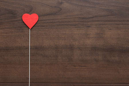 wooden stick: red heart shape on stick over wooden background Stock Photo