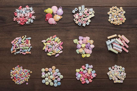colorful beads: different colorful beads on the brown wooden table Stock Photo