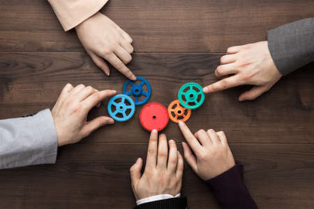 Teamwork concept. Different hands of men and women connect colorful gears into working mechanism on the brown wooden table background. Each has its own role in problem-solving. Experience exchange