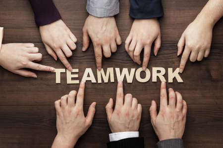 teamwork concept: Teamwork concept. Different hands of men and women connect letters into one word on the brown wooden table background. Each has its own role in team Stock Photo