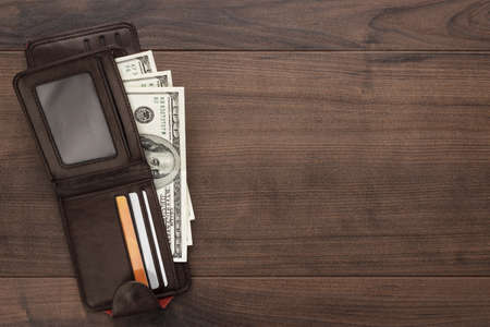 notecase: mens purse with money, credit and debit cards on the wooden table