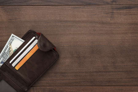 morenas: bolso de los hombres con dinero, tarjetas de crédito y débito en la mesa de madera