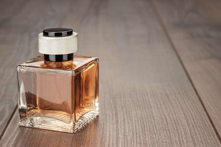 Butelka perfum na brązowym drewnianym stole tle