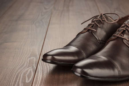 formal wear clothing: brown leather shoes on the wooden background